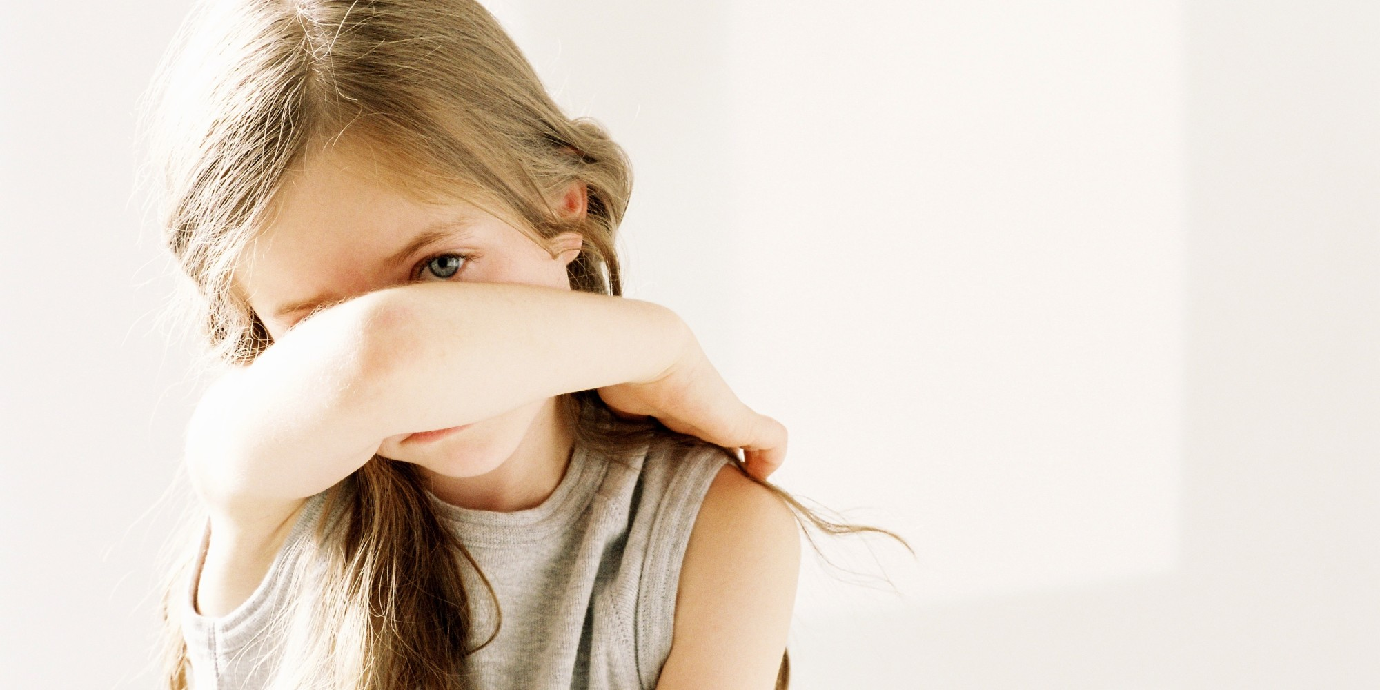 Girl with long hair anxiously holding her arm in front of her face